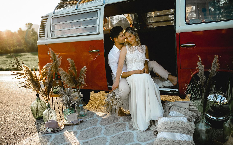 Das Brautpaar sitzt im Bulli und posiert für die Hochzeitsfotos. Deko aus Pampasgras steht neben dem Wagen.