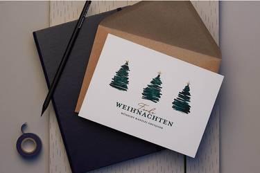 Eine veredelte Weihnachtskarte für geschäftliche Anlässe, drapiert auf einem Notizbuch.